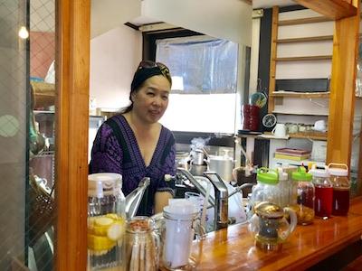 店主のカヤさん カウンターに並ぶのは酵素ジュースボトルや紅茶キノコ