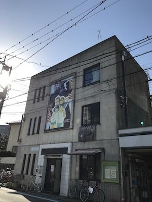 壁に大きなイラストが描いてあるこのビルの2階です