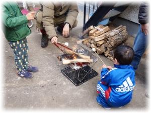 長い竹串に刺したマシュマロを火で炙ってます