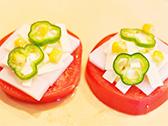 トマトの上に、もち、小さくちぎったスライスチーズ、コーン、ピーマンをのせて、塩をふってオリーブオイルをたらし、トースターで7分前後焼く。