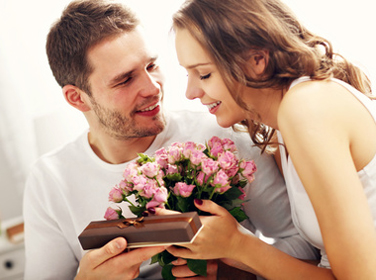 Man giving flowers and present to woman in bed