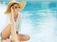 Portrait of beautiful tanned sporty slim woman relaxing in swimming pool spa.