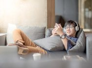 Young Asian man using smartphone taking a break relaxing on sofa during study in library, high school or university college student, educational concept