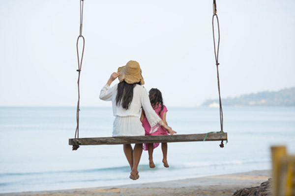 ビーチのブランコで遊ぶ親子