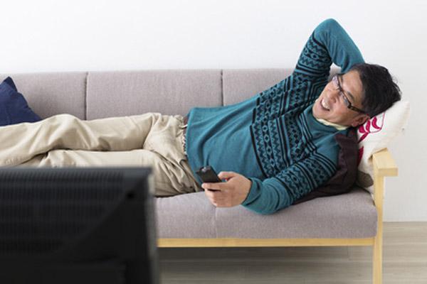 くつろいでテレビを見るミドル男性