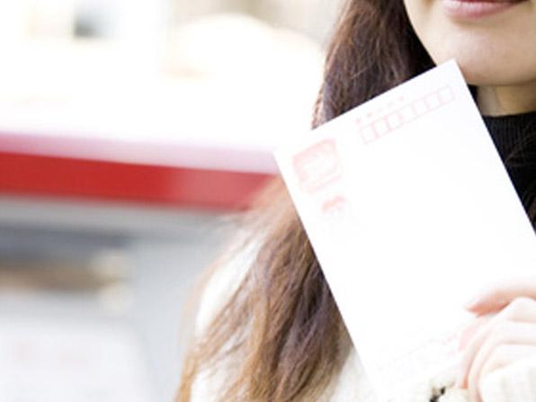 年賀状をポストに入れる女性の手